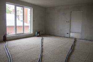 natiahnuté rozvody kúrenia v obývacej izbe bytu